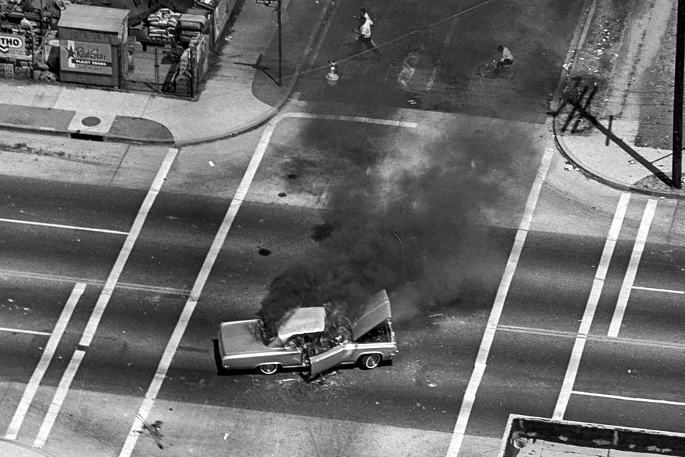 Aug. 13, 1965: Car burns in intersection of Avalon Blvd. during Watts Riots. Cross street unknown. Unpublished image.
